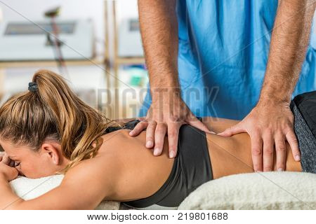Physical therapy. Therapist applying strong pressure onto lower back muscles
