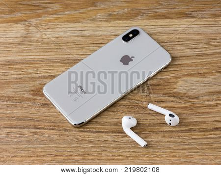 Rostov-on-Don, Russia - December 12, 2017: The Iphone 10 lies on a wooden table next to the wireless headphones airpods from the Apple.