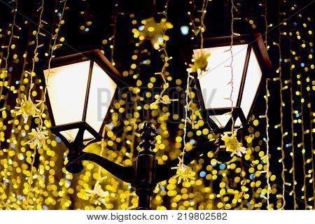 Metal lantern on background of neon garland, as yellowed leaves, vintage tones. Fall and fest backdrop. Concept nostalgic mood, melancholy, festive occasions