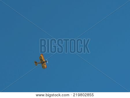 Biplane Flies Over with Copy Space on Cloudless Day