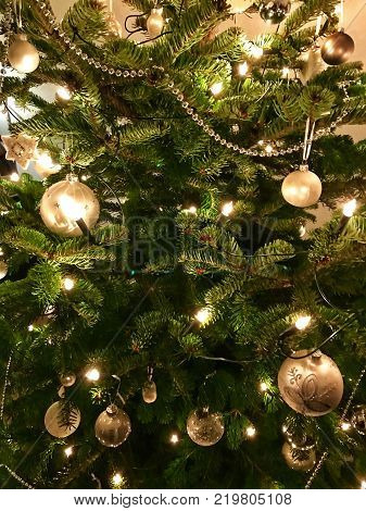 Closeup of Christmas-tree decorated with white and silver Christmas baubles
