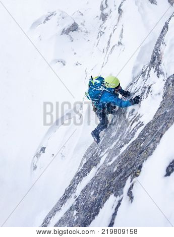 Girl in the storm during an extreme winter climb. West italian Alps, Europe.