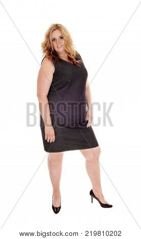 A beautiful woman in her thirties standing in a black dress and high heels with long blond hair isolated for white background