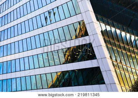 Skyscraper exterior design. Abstract view of window, mirror reflection and detail architecture close-up. Modern office building, glass facade. Business center. Urban view, looking up, glass skyline.