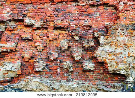Damaged brick wall of red color. Vintage background, old weathered texture. Shabby surface of grunge masonry. Exposed vintage building exterior facade.