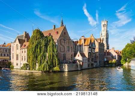 Unidentified tourists visit the medieval city of brugge using the typical boats over canals in Belgium, Brugge, October, 01, 2014.