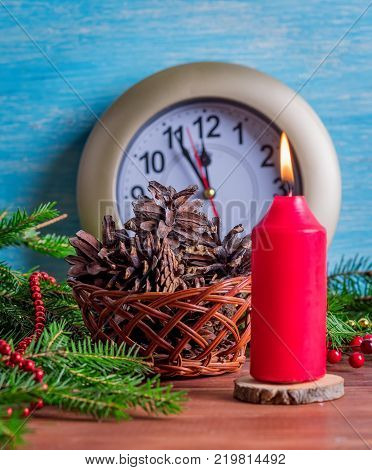 Watch with the last minutes of the outgoing year a large red candle and a basket of cones.