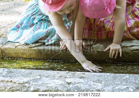 Two girls playing with water in a creek on a hot sunny day
