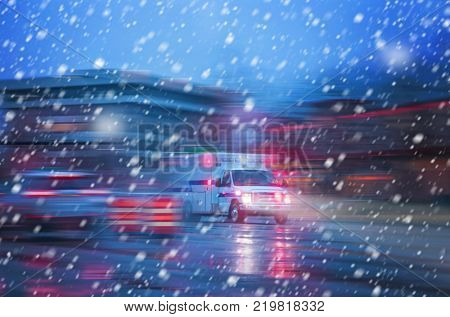 an ambulance racing through the rain on a stormy night with motion blur (NO SHARP FOCUS DUE TO SNOW) with reflections in the road