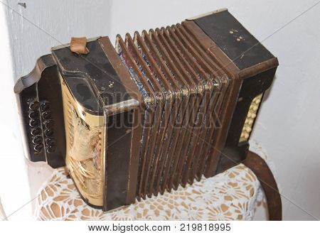 Old dusty accordion. Musical instruments of the Russian village.