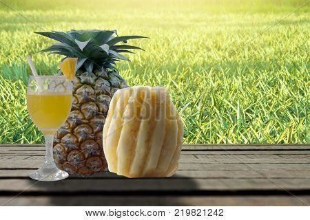 Pineapple Juice Glass And Pineapple Fruit Products On Wooden Table With Pineapple Green Plant Backgr