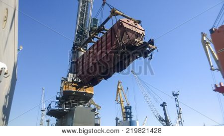 Novorossiysk, Russia - August 11, 2016: Moving freight railway car in the port by a port crane. Cargo lifting operations. Industrial port.