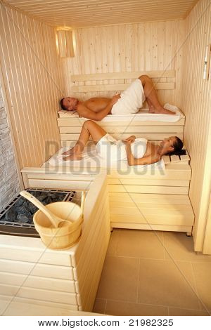 Man and woman lying in sauna, relaxing on wellness.