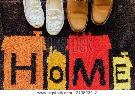 Welcome Home Carpet With Shoes On It.