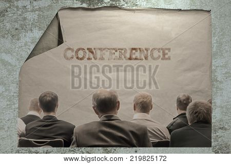 old paper on a cement wall with an unrecognizable people sitting rear at the business conferece and inscription conference. busines concept.
