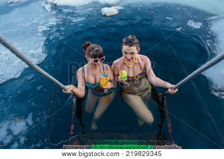 Novokuznetsk, Kemerovo region, Russia - 23 Feb, 2017 : White beaches of Siberia is an enterteiment activity where people playing beach games dressed in bikini in winter. Women in ice hole with drinks