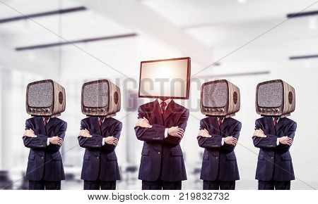 Businessmen in suits with old TV instead of their heads keeping arms crossed while standing in a row and one at the head with TV inside office building.