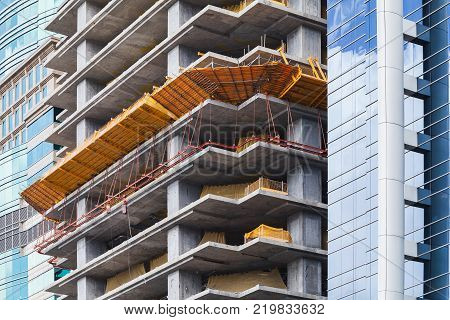 Modern office building is under construction concrete floors. Facade fragment with scaffolding structures