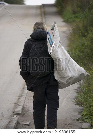 Dirty homeless man holding Lifestyle of tramp living in the streets. poster