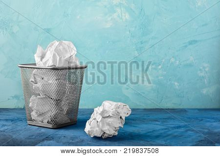 A trash can with papers, one lump is lying next to it. Beautiful unusual background with place for text. Full basket.
