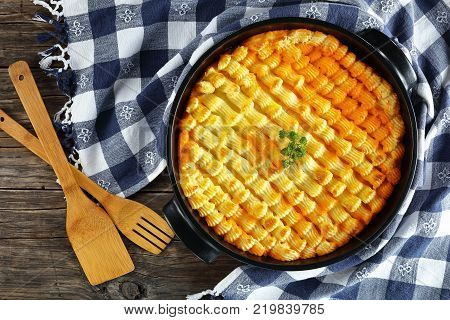 delicious shepherd's pie or cottage meat pie in baking dish on dark wooden table with kitchen towel and wooden spatulas authentic recipe of english cuisine horizontal view from above