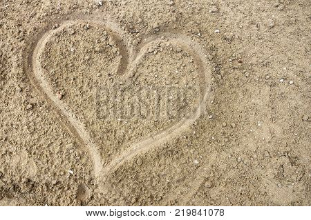 Drawing a heart on the wet sand at the sea. Top view. Ideal for concepts and background. Saint Valentine's day.