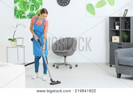 Young woman hoovering floor at home