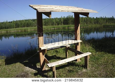 A wood gazebo over looks the River in on a blue sky day