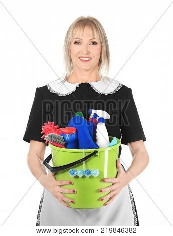 Mature charwoman with cleaning supplies on white background