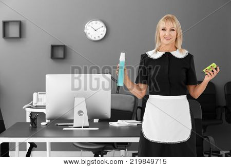 Mature charwoman with bottle of detergent and sponge for cleaning office