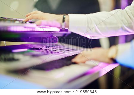 Double Piano Synthesizer On Stage With Purple Lights.