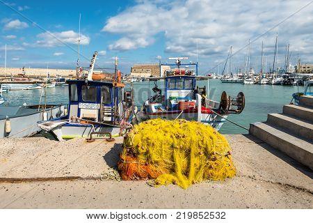 Heraklion Greece - November 2 2017: Fishing nets and fishing boats near Venetian fortress in the port of Heraklion Crete Greece.