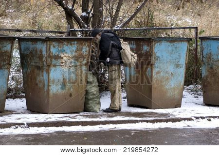 Homeless old man in search for food. Poor tramp hungry rummaging for some food in garbage.