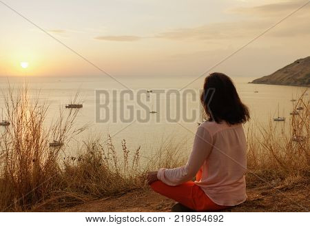 a Young girl sitting in yoga lotus meditation position in front to seaside on the rocks an watching the sun goes down in a golden hour. sunset over sea.