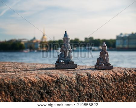 Figures of small sphinxes stand on the granite embankment of the Neva River with a view of the sights of the city of St. Petersburg on a summer day illuminated by the sun poster