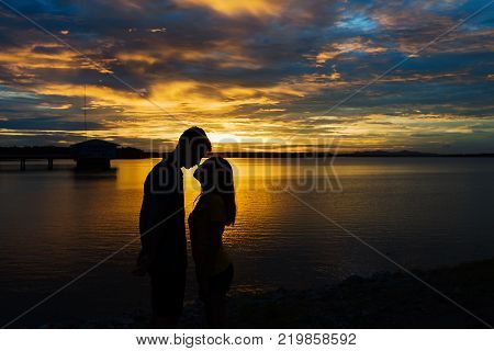 Silhouette couple in love at lake during beautiful sunset.relaxing concept.