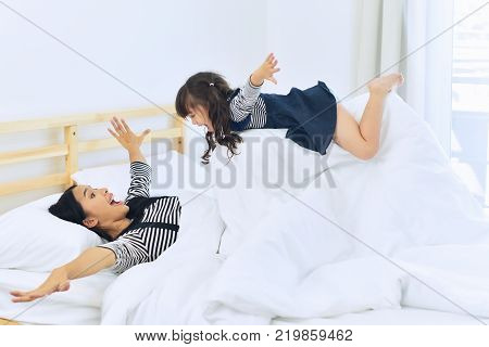 Mother and her child girl playing together on the bed.Happy family.relaxing and family concept.
