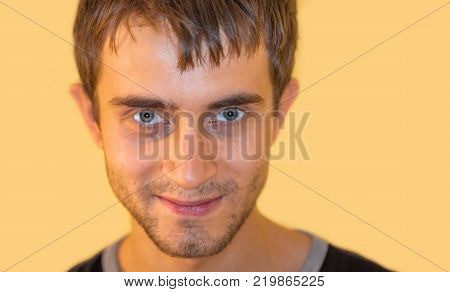 Happy young man. Closeup portrait of a charming young man with an eyelash on his cheek isolated on yellow background with copyspace. Trendy colors.
