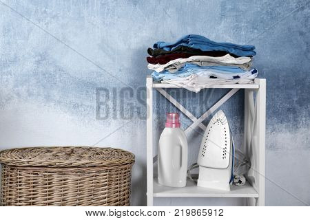 Laundry, iron and detergent on shelving unit