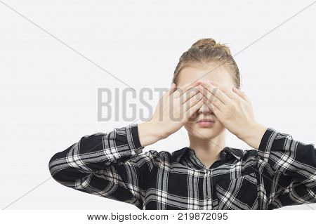 I cant see you -- Young Women is covering her eyes with her hands.Young beautiful girl closing her eyes with her hands. On a white background.