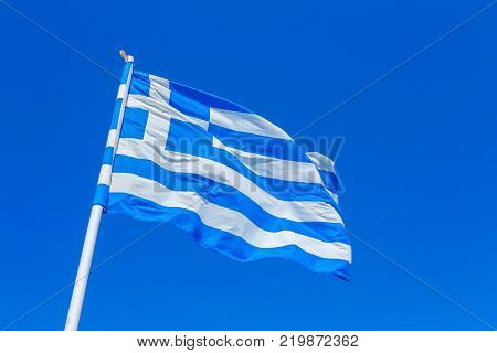 Greek flag in the wind against a blue Summer sky