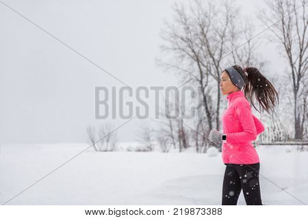 Winter running woman in cold snow weather jogging outside wearing windproof clothes with gloves, headband, winter tights and wind jacket in white snowing storm background.