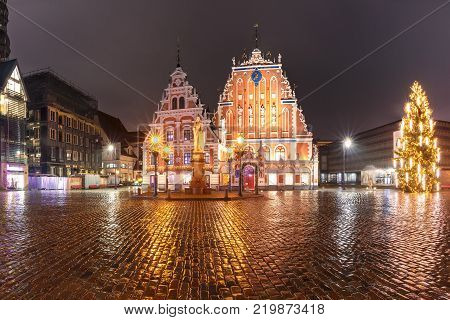 City Hall Square with House of the Blackheads, illuminated Christmas tree and Saint Roland Statue in Old Town of Riga at night, Latvia