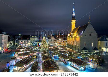 Decorated and illuminated Christmas tree and Christmas Market at Town Hall Square or Raekoja plats, Tallinn, Estonia. Aerial view