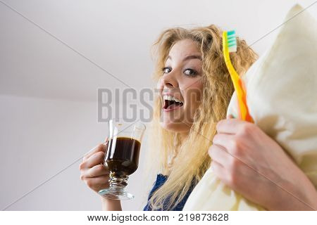 Funny woman holding black coffee and toothbrush being late. Getting morning energy hurry up before going to work.