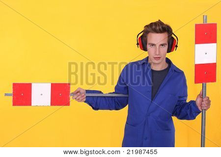 Man in ear defenders with warning signs