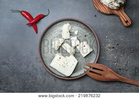 Plate with cheese and cooking utensil on grey background