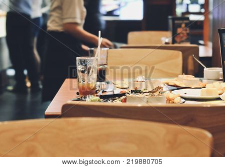 Person holding collecting in hands dirty dishes restaurant background, waitress working in restaurant, working concept.