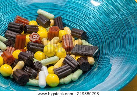 Treat bowl. Sweet candy liquorice pieces in modern blue bowl.Colorful close up image.
