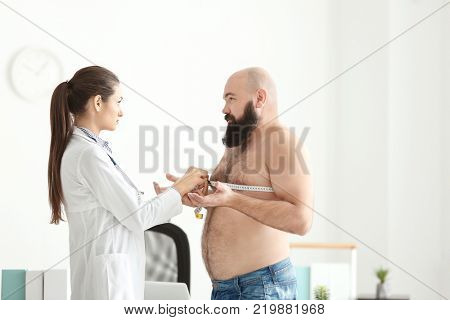 Young female doctor measuring chest of overweight man with centimeter in clinic